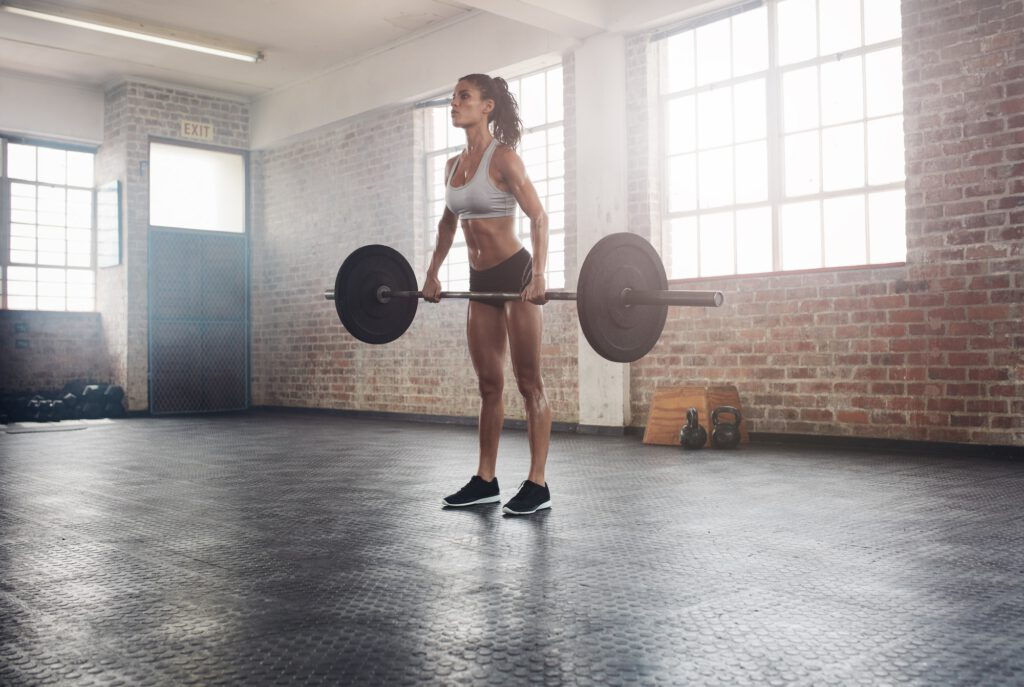 Fit female athlete lifting weights in gym