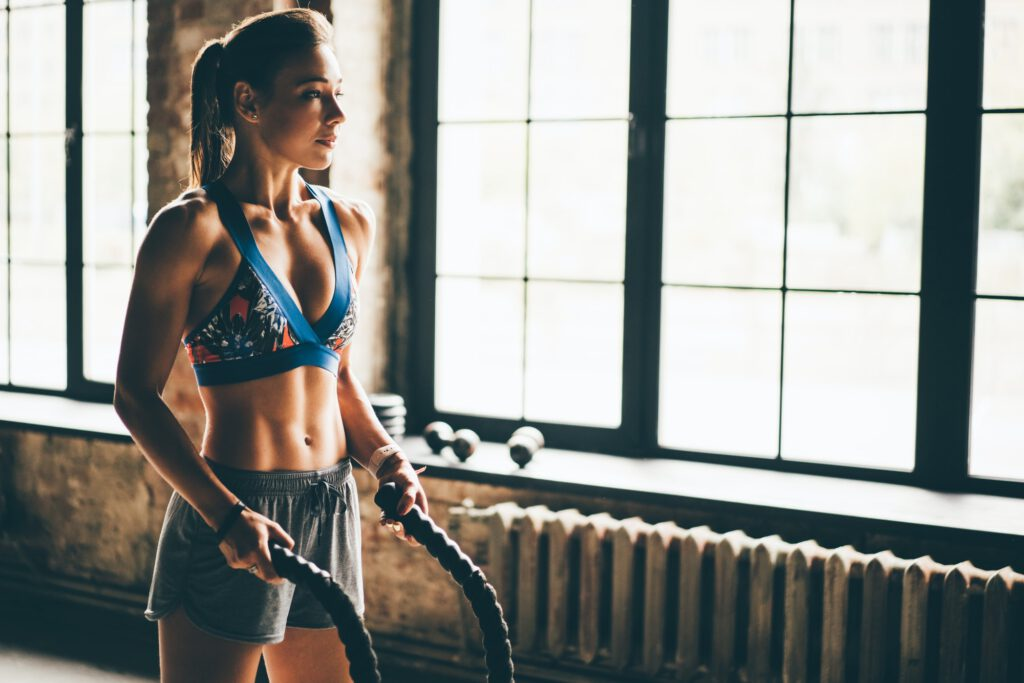 Fitness woman exercising with battle ropes at gym.