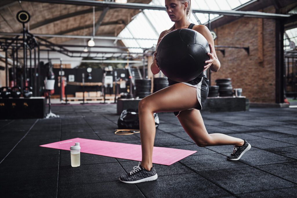 Woman working out with a fitness ball at the gym