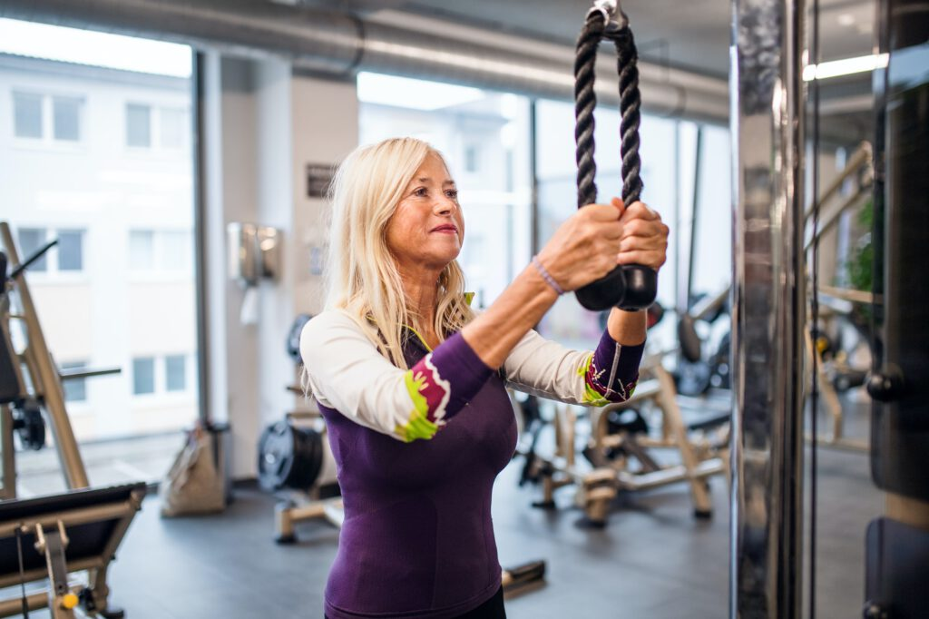 A portrait of senior woman in gym, doing exercise